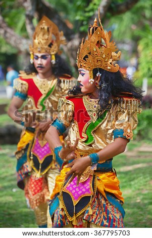 BALI ISLAND, INDONESIA - JUNE 20, 2015: Group of young men dressed in colorful ethnic Balinese people costumes, dancing traditional ritual temple dance at Art and Culture Festival. - stock photo