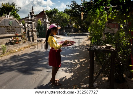BALI, NUSA PENIDA ISLAND, INDONESIA - JULY 28, 2015: Balinese girl with offerings in front of home temple on July 27, 2015 in Nusa Penida, Indonesia - stock photo