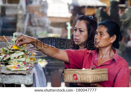 BALI - SEP 25. Local woman carrying offering to local temple for on Sept 25, 2012 in Bali, Indonesia. Offering flowers and other gifts is very popular tradition on Bali. - stock photo