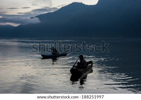 Balinese fishermen fish in traditional paddle boats in the morning before sunrise on this volcano crater lake in Bali, Indonesia. - stock photo