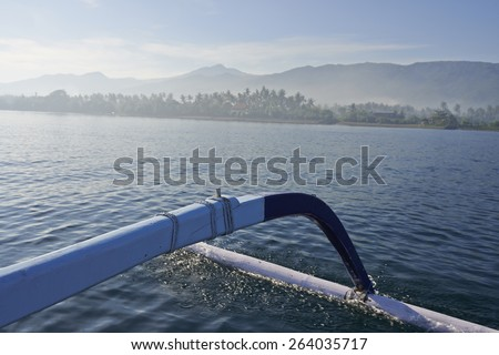 balinese fishing boat coming back to island early in the morning - stock photo