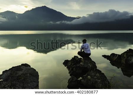 Balinese man resting on rock boulder enjoying serene cloudy morning sunrise at Lake Batur Bali Indonesia. - stock photo