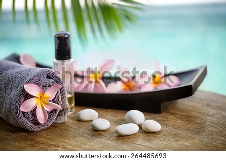 Balinese spa setting, pink frangipani with aromatherapy oil  - stock photo