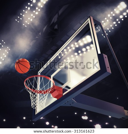 Ball above the basket during basketball game - stock photo