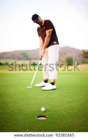 Ball near the hole and golfer on background - stock photo