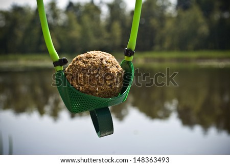 Ball of groundbait in slingshot ready to shoot and feed fish. Fishing concept - stock photo