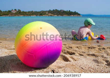 Ball on the beach and little boy playing in the shallow sea water - stock photo