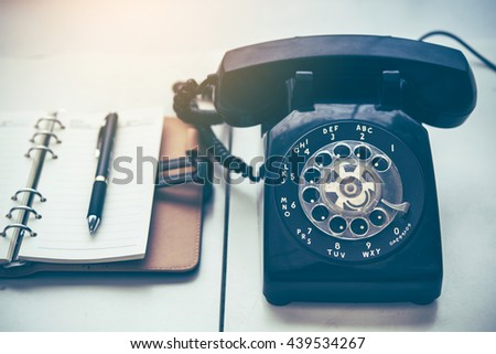 Ball point pen on notebook with old black phone, retro style concept  - stock photo
