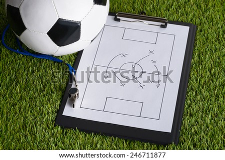 Ball; Whistle And Soccer Tactic Diagram On Paper Over Pitch - stock photo