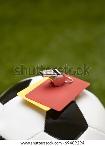 ball, whistle and warning cards in soccer field - stock photo