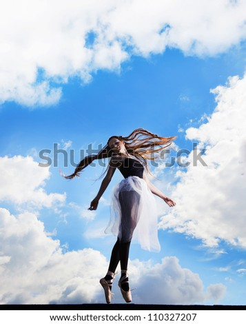 Ballerina dancing on the roof, clouds behind her - stock photo