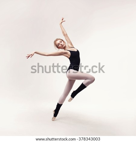 Ballerina in black outfit posing on toes over light grey studio background. - stock photo