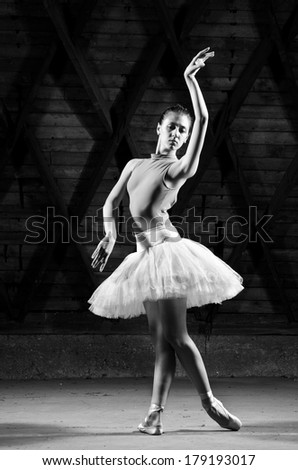Ballerina in white tutu posing on dark background. Black and white image - stock photo