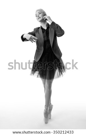 Ballerina model en pointe, holding a phone to her left ear and her right arm poised ready to dance - stock photo