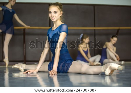 Ballerina sitting on the floor in the splits in a dance class dancers practicing on the background. Dancer is smiling. - stock photo