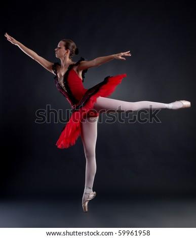 ballerina wearing red tutu posing on studio background - stock photo