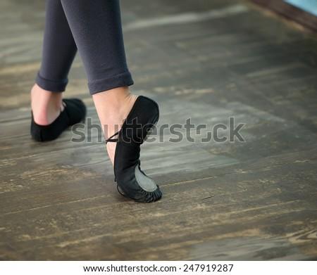 Ballerinas legs in black pointes on wooden floor in point position - stock photo