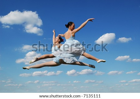Ballerinas performing outdoors against a blue sky - stock photo