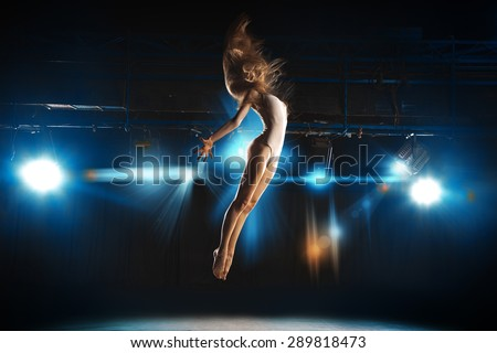 Ballet dancer fly on stage in theater against spotlights - stock photo