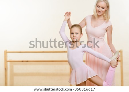 Ballet lesson. Young female teacher helping her little apprentice to learn new move and hold the pose. - stock photo
