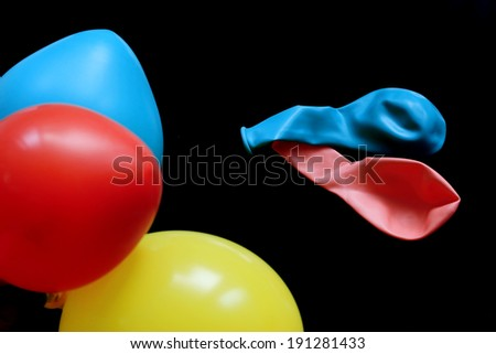balloons in primary colors on black background - stock photo
