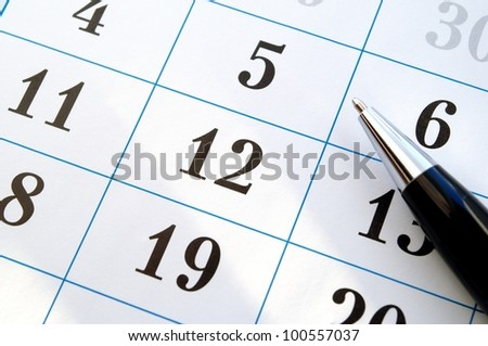 ballpoint pen and a calendar of close-up - stock photo