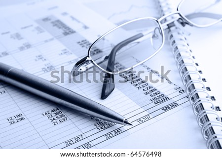 Ballpoint pen,glasses and financial report - stock photo