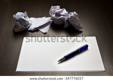 Ballpoint pen on a clean paper and crumpled described papers - stock photo