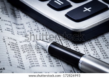 Ballpoint pen resting on world currency figures - stock photo