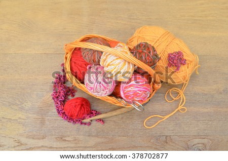 Balls of colored wool yarn in a basket on wooden background. Flat lay - stock photo