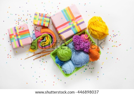 Balls of colored yarn. View from above. All the colors of the rainbow. Sample knit. Crochet. Gifts wrapped in colored paper. Holiday packages show. - stock photo