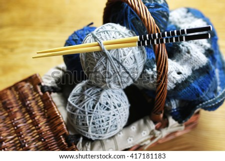 balls of wool and knitting needles on a wood background - stock photo