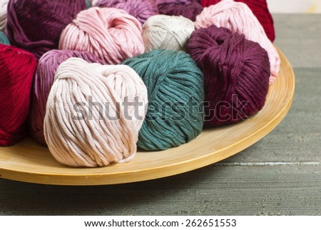 balls of wool on bamboo dish, rusty wood table background - stock photo