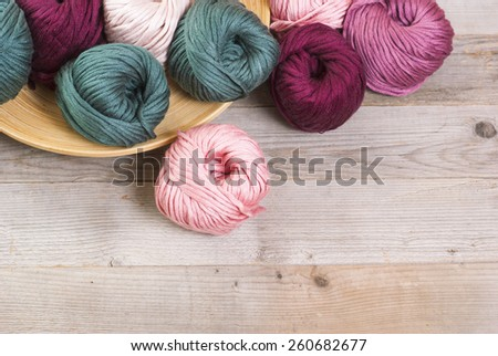 balls of wool on bamboo plate, old wood table - stock photo
