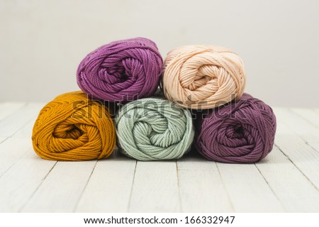balls of wool on white wood surface - stock photo