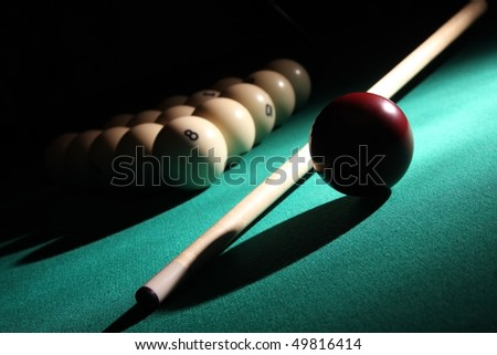 Balls pyramid with number 8 ball on a foreground, cue and red ball on a light beam. - stock photo