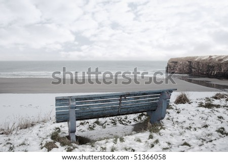 ballybunion bench in winter with view of beach and cliffs - stock photo