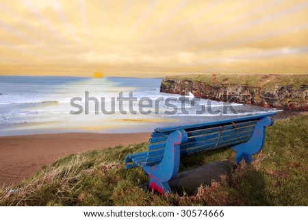 ballybunion bench in winter with view of beach and cliffs as the sun sets - stock photo