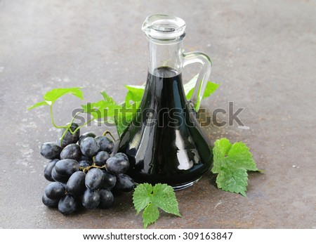 balsamic vinegar in a glass jug with fresh grapes - stock photo