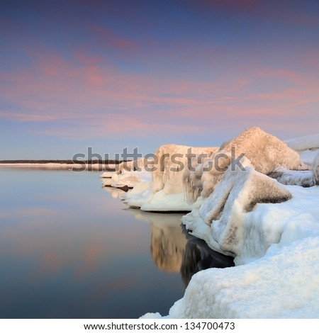 Baltic sea shore in snowy winter at the sunset - stock photo