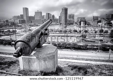 Baltimore Maryland Inner Harbor downtown cityscape skyline with National Aquarium and boat marina from Federal Hill Park overlook with Civil War cannon - stock photo