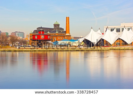 Baltimore waterfront with Seven Foot Knoll Lighthouse at sunset in winter. Colorful reflections of waterfront buildings at Inner Harbor in Baltimore, Maryland. - stock photo
