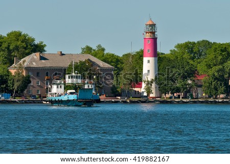Baltiysk, Russia - June 29, 2010: Nida ferry boat on Baltic Spit for cars and people over old lighthouse background. ex-Pillau. Kaliningrad region - stock photo