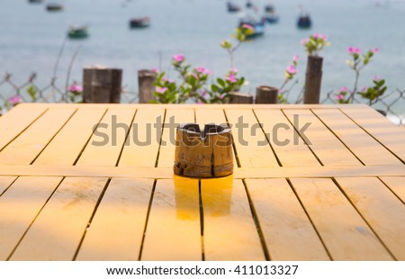 Bamboo ashtray on wooden yellow paint table on the beach - stock photo