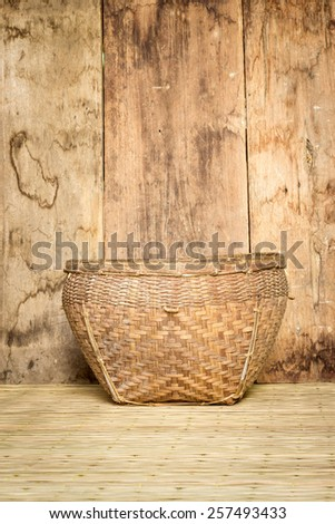 bamboo basket on mat weave and wood board background - stock photo