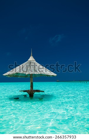 Bamboo beach umbrella with bar seats in the water of tropical island - stock photo