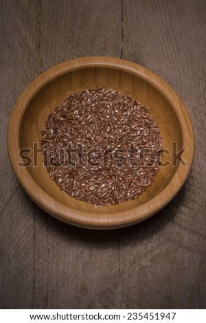 Bamboo bowl with brown flax seed or linseed on wooden background - stock photo