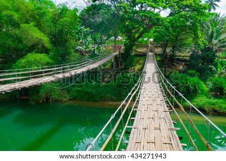 Bamboo hanging bridge over river in tropical forest, Bohol, Philippines - stock photo