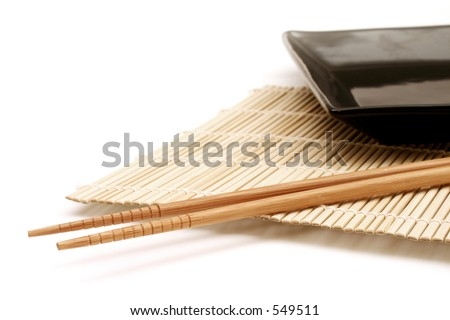 Bamboo mat, dish and chopsticks - stock photo