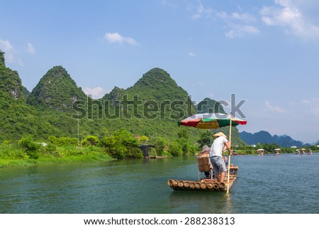 Bamboo rafting in the Yulong River surrounded by dramatic landscape of limestone karst.  - stock photo